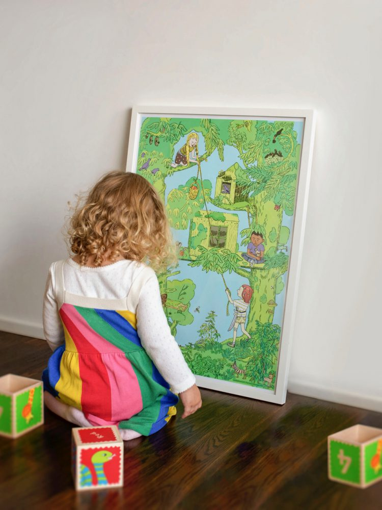 A child is fascinated by a print with tree houses and children