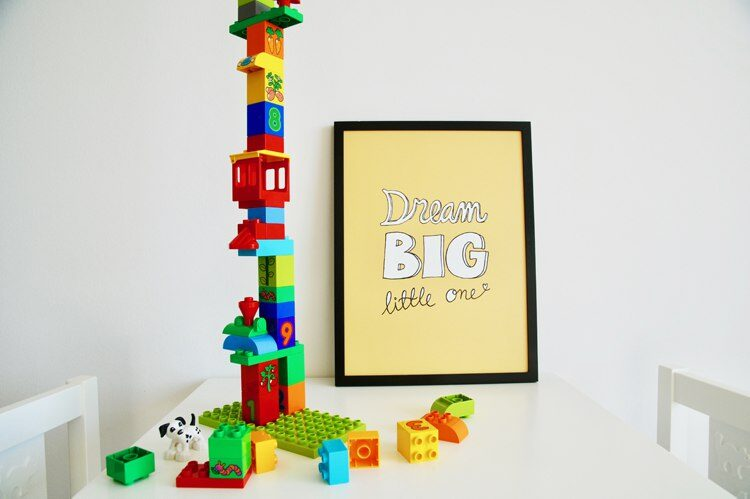 Yellow poster with the text 'Dream big little one' placed on table with colourful duplo lego bricks