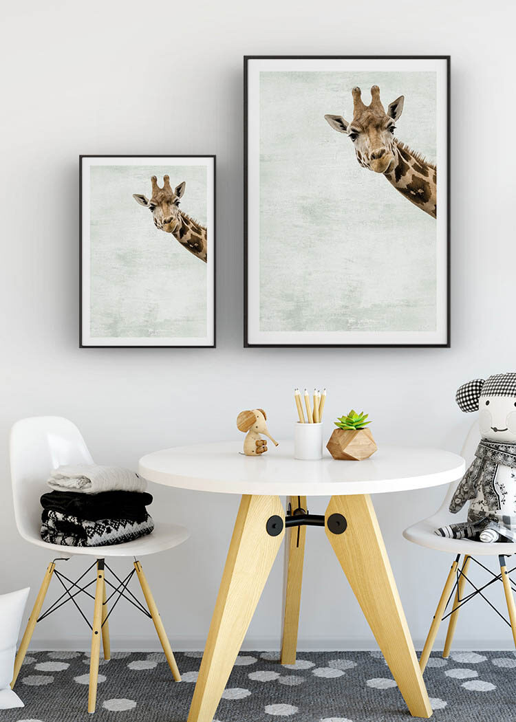 Two giraffe prints on wall behind table and chairs in child's size