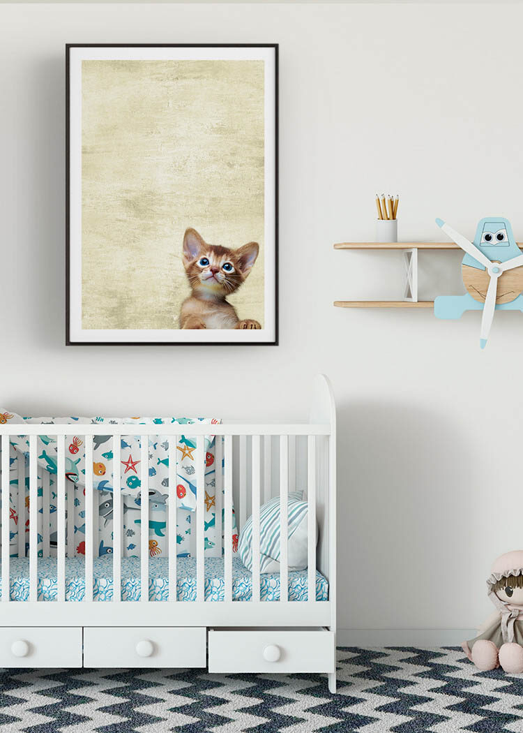 Young cat poster above crib and next to toy plane