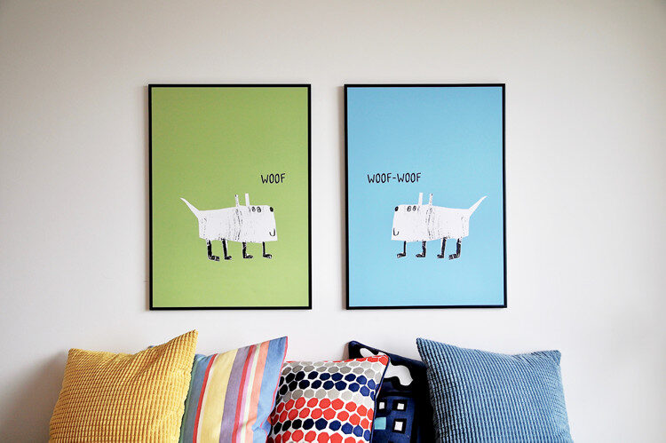 "Prints with illustrated dogs and the text ""Woof"" mounted on wall with pillows in front"