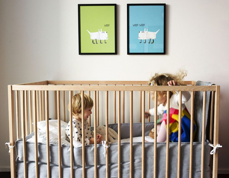 Two illustrated posters with dogs and Woof text on wall with crib with children playing