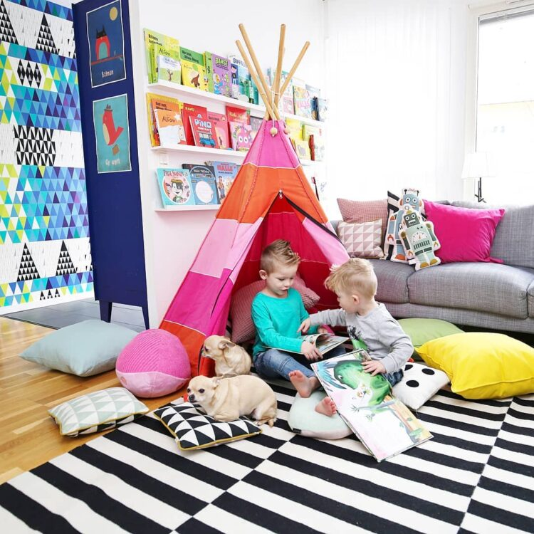 Batman and Go Work posters in living room with children in a tent reading