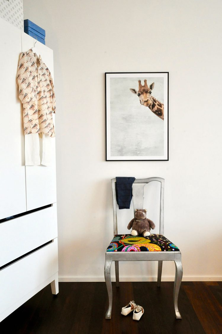 Poster in black frame with giraffe on wall in child's room with silver chair, hippo plush toy and shirt with birds