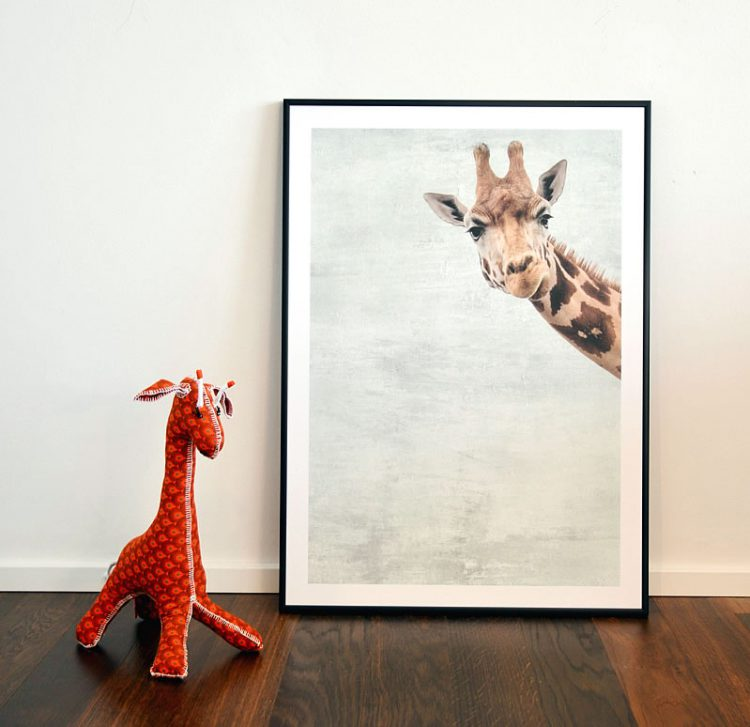 Giraffe poster in black frame with with orange plush giraffe toy
