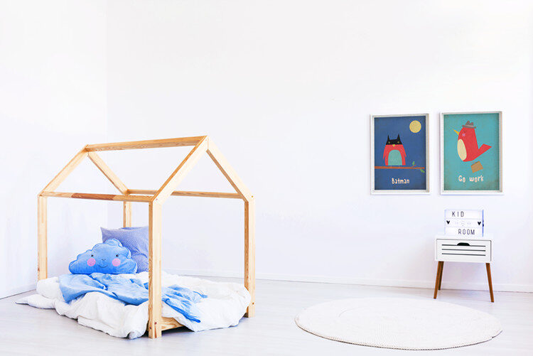 Kids paintings with own in Batman mask and bird with portfolio on wall in room with wooden bed and blue cloud pillow