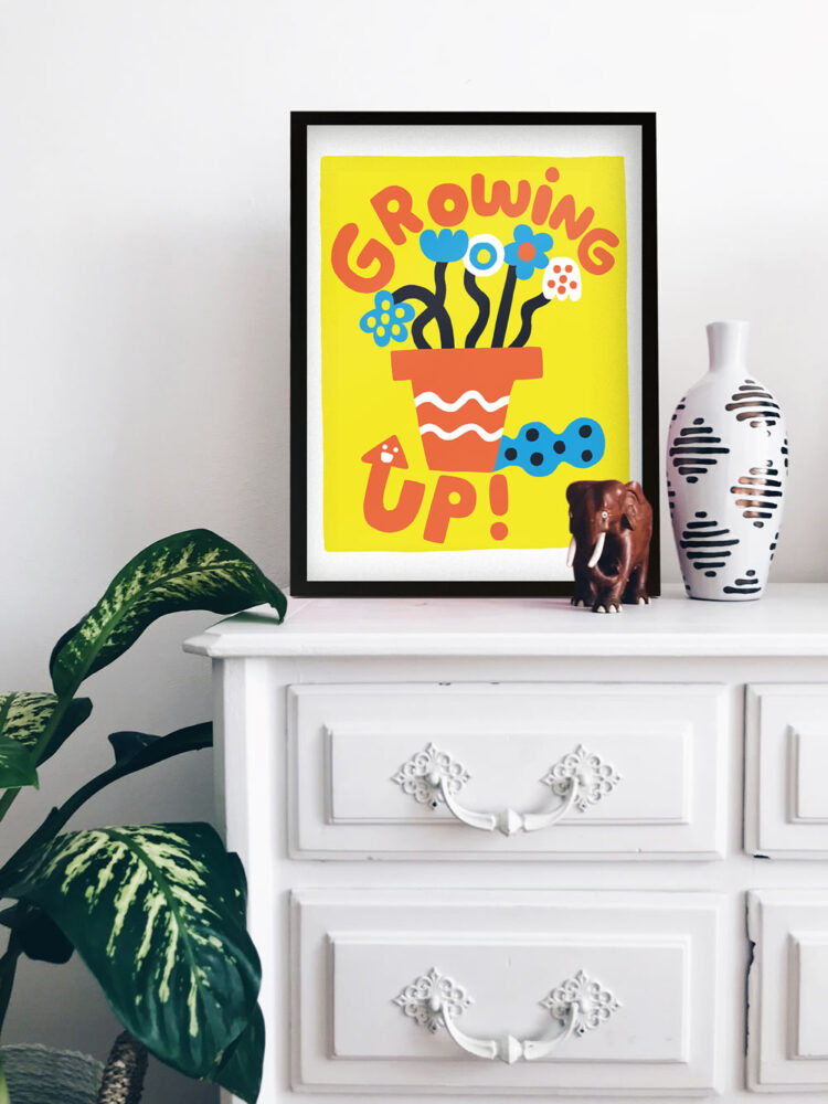 Growing Up! poster on white sideboard with elephant figurine