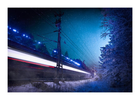 Quick train in blue and red in winter landscape with snow on trees and powerlines