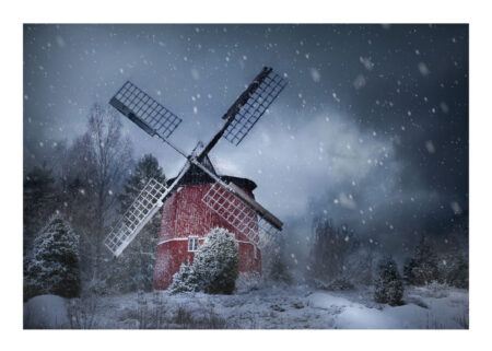 Red wooden wind mill with black wings in snowy Swedish landscape with juniper bushes and cloudy bluish gray sky