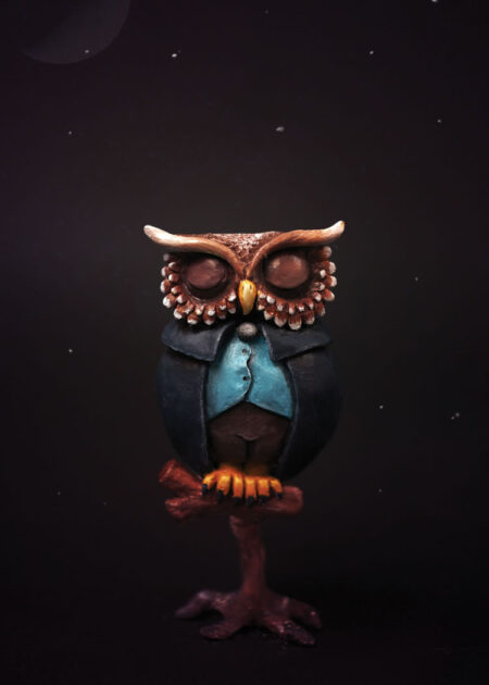 Clay figure Owl with closed eyes in blue jacket on small stick by Elisabeth Karin